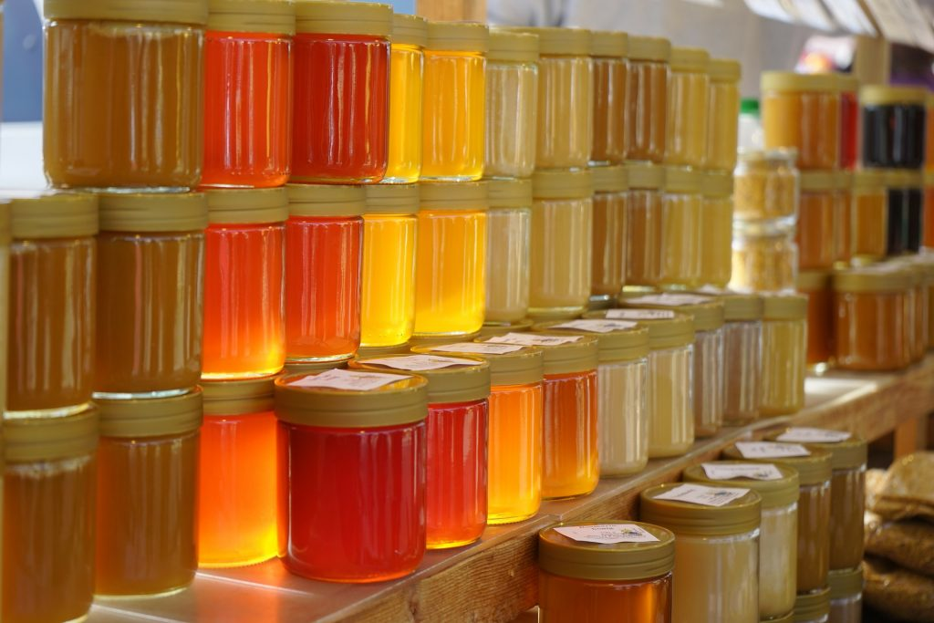 different types of honey jarred and packaged to prepare for sale